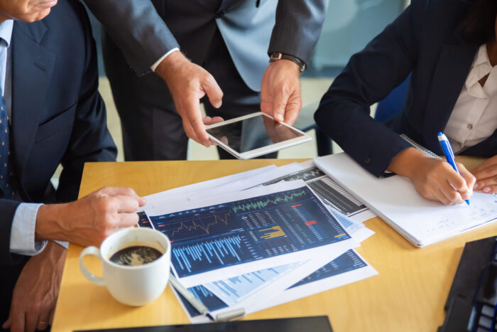 Unrecognizable business partners working with statistic charts. Businessman holding tablet. Professional content businesswoman making notes for statistics. Communication and partnership concept